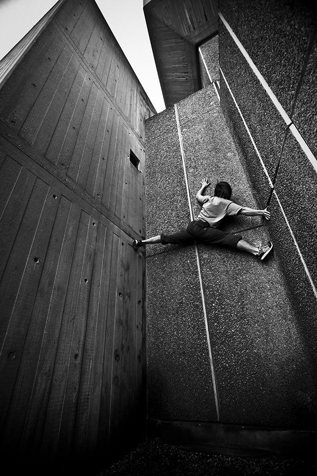 Ein Mann im Spagat an einer Mauer.