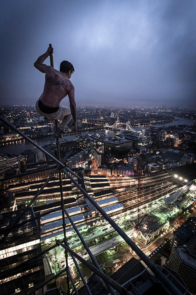 Ein Mann sitzt auf einem hohen Gerüst über der nächtlichen Stadt.