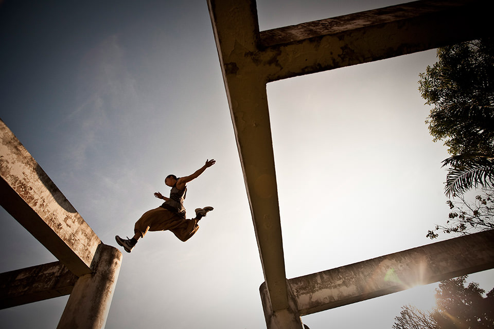 Ein Mann spingt von einem Betonpfeiler auf einen anderen.