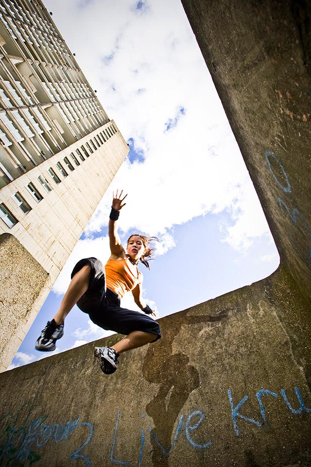 Eine Frau springt von einer Mauer.