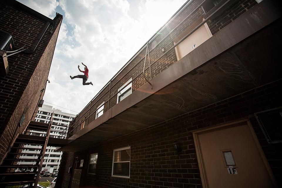Ein Mann springt von einem Haus zum anderen.