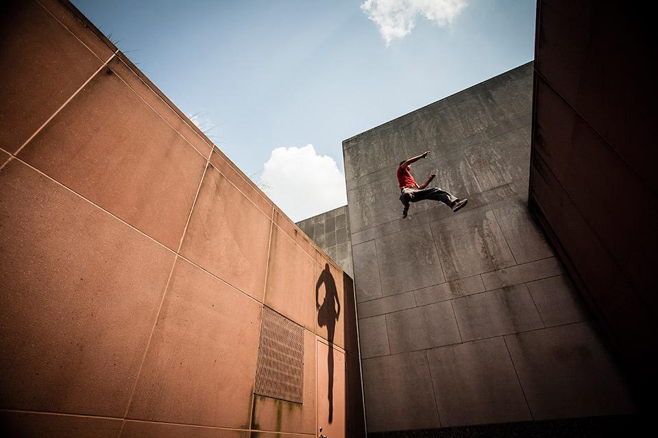 Ein Mann klettert an einer Hauswand.