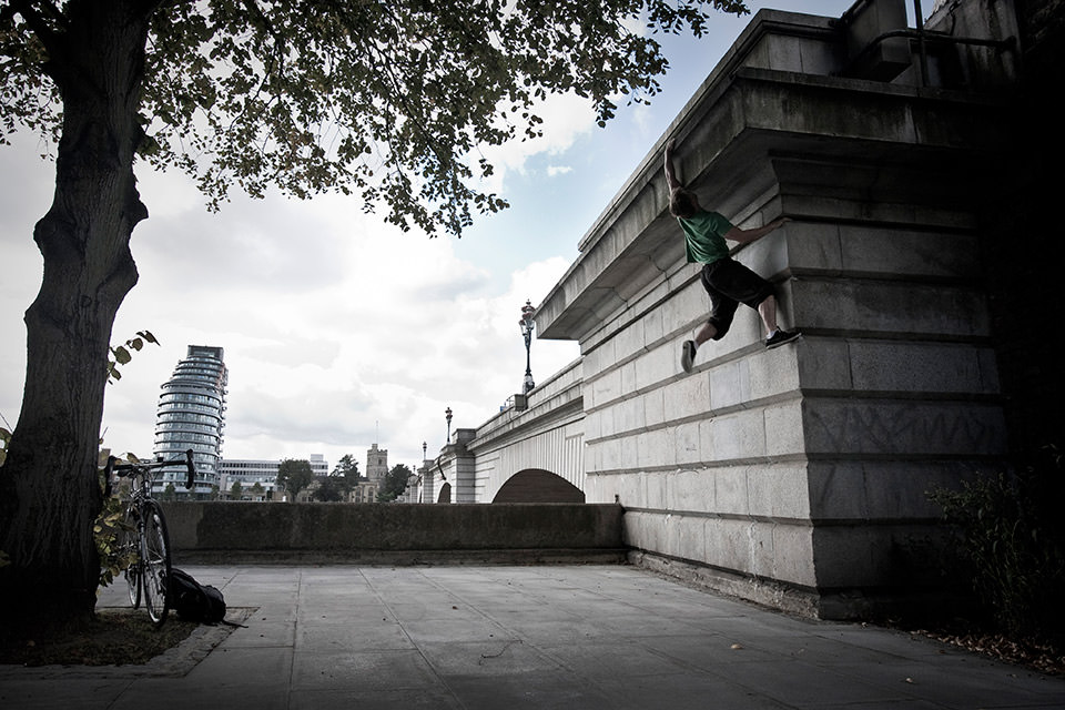 Ein Mann springt an eine Mauer.