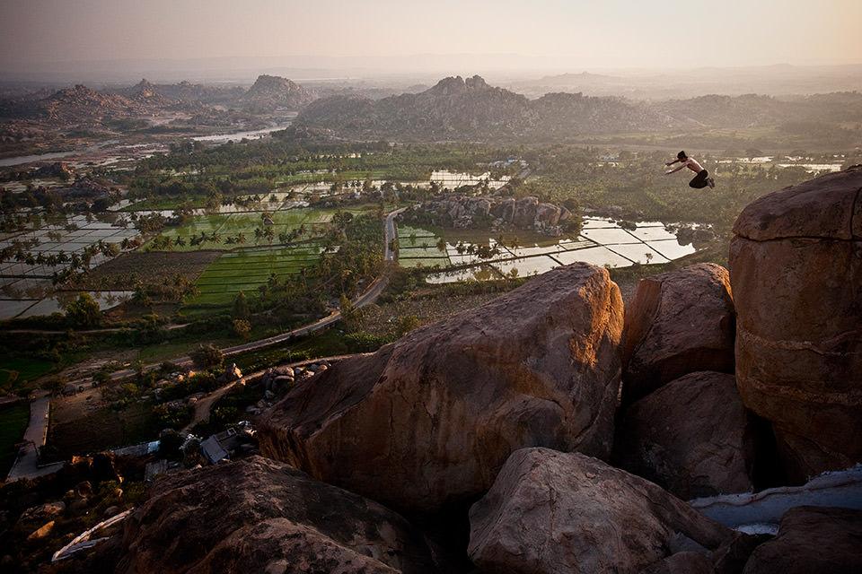 Ein Mann springt von einem Felsen.