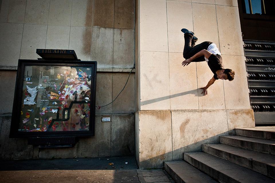 Ein Mann springt von einer Mauer auf eine Treppe.