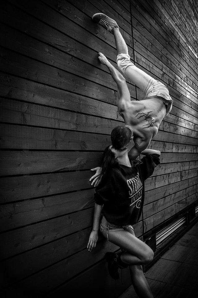 Ein Mann hängt kopfüber an einer Mauer und küsst eine darunter stehende Frau.