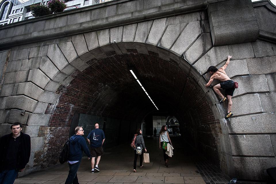 Ein Mann klettert über einem Tunneleingang. Darunter gehen Passanten.