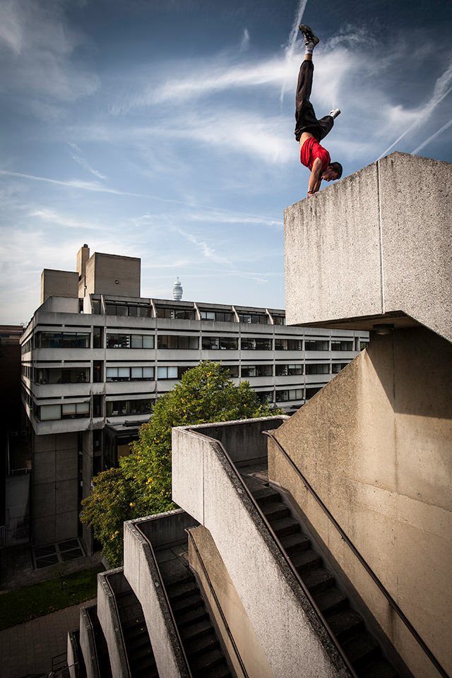 Ein Mann macht Handstand auf dem Rand eines Gebäudes.