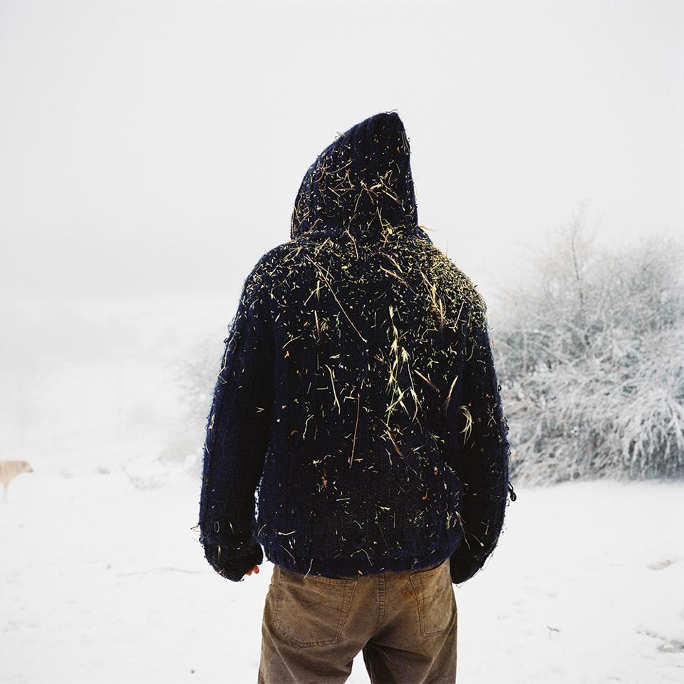 Mensch von hinten mit Strohresten auf dem Pullover