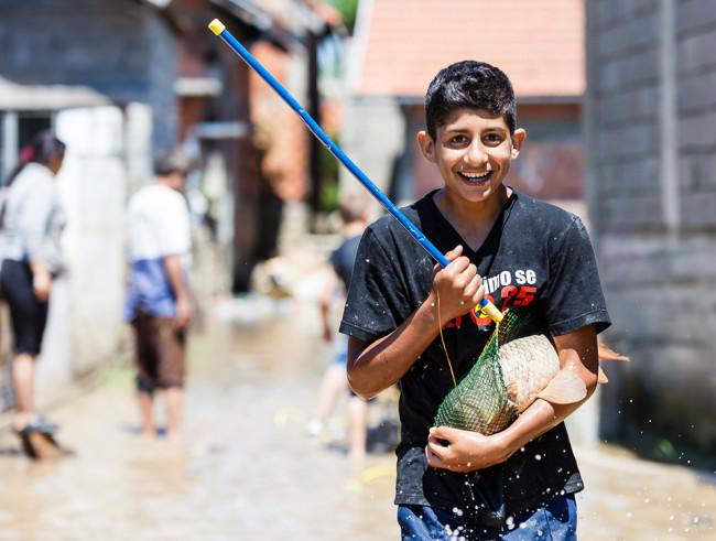 Ein Junge mit einem Fisch in der Hand.