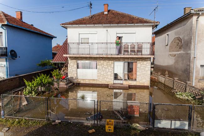 Ein überflutetes Haus, ein Kind steht auf dem Balkon und schaut zum Fotografen.