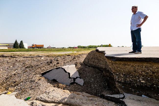 Ein Mann schaut in die Ferne und steht auf einer zerstörten Strasse.