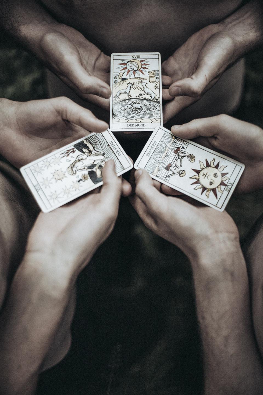 Sechs Hände halten drei Karten zueinander.