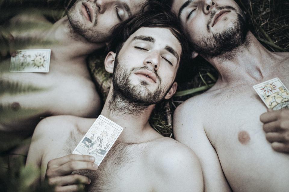 Drei Männer liegen auf dem Waldboden und halten vor ihre Brust Tarotkarten.