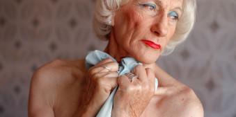 Eine ältere Frau mit weißen Haaren und rot geschminkten Lippen schaut versunken weg.