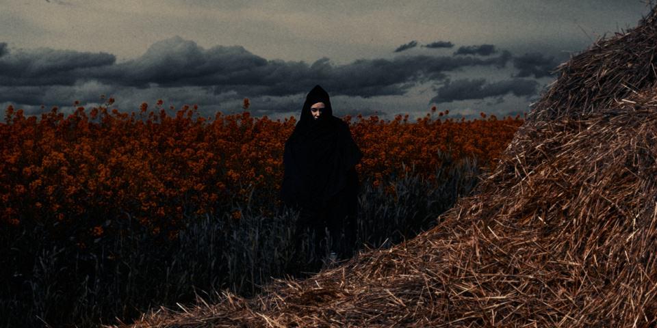 Ein Mensch mit Umhang vor einem roten Feld.