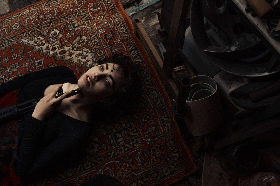 Eine Frau liegt auf dem Boden und hält sich einen Gewehrlauf unters Kinn.