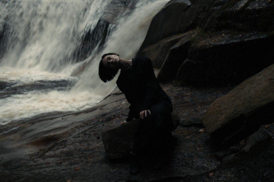 Eine Frau vor einem Wasserfall.