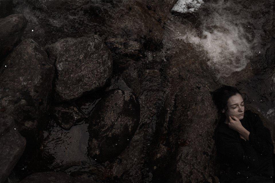 Eine Frau liegt auf nassen Steinen.