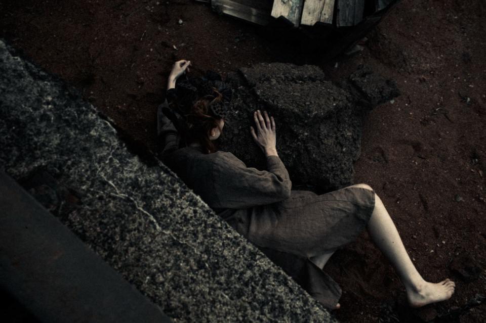 Eine Frau zwischen großen Steinen.