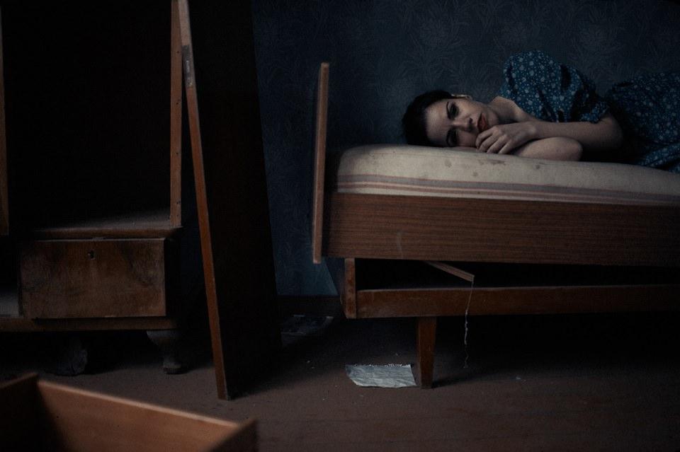 Eine Frau liegt auf einem kaputten Bett.
