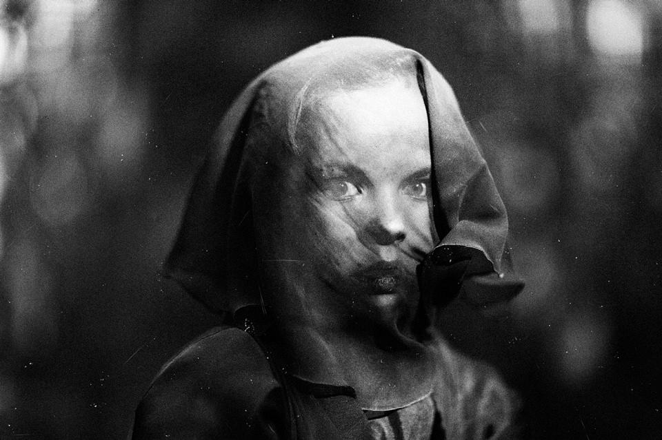 Ein Kind blickt eindringlich durch Tuchstoff.