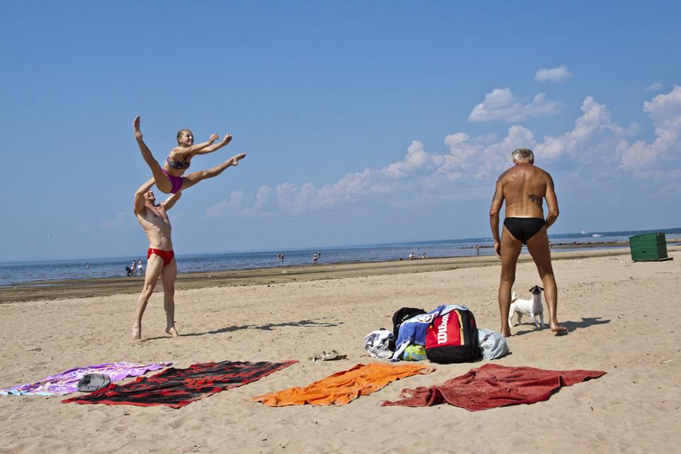 Drei Menschen in Badebekleidung am Strand.