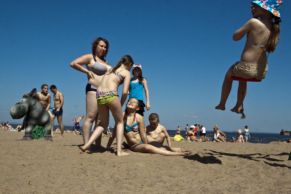 Menschen in Badebekleidung am Strand.