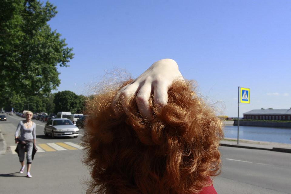 Eine Person greift sich in ihr lockiges Haar.