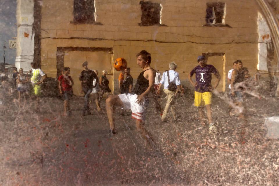Junge Männer spielen Fußball, betrachtet durch eine Scheibe.