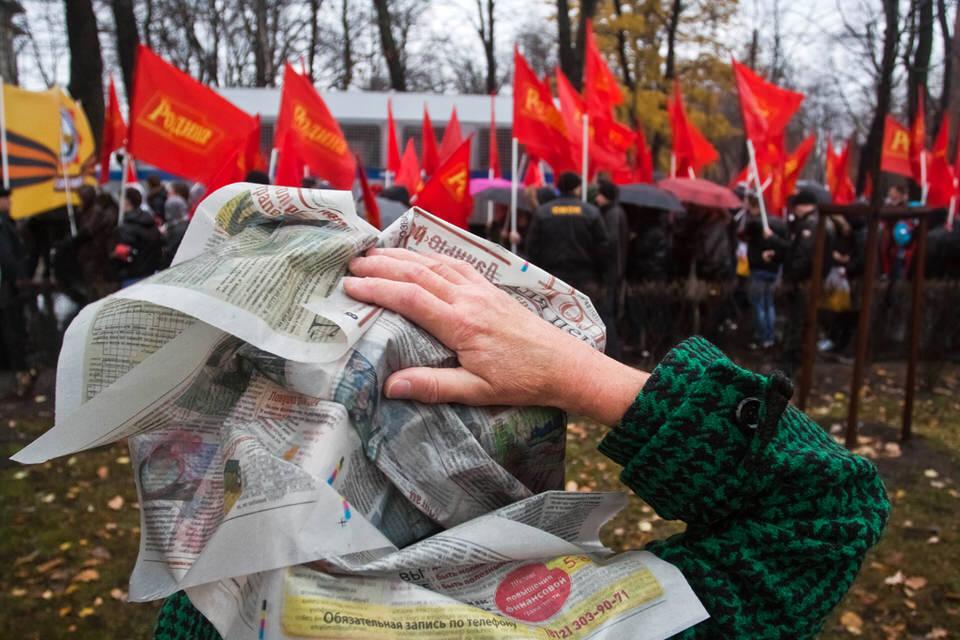 Eine Person hält sich Zeitung auf den Kopf, im Hintergrund rote Fahnen.