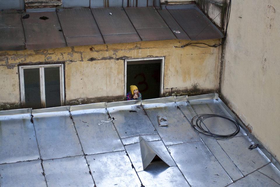 Ein Mädchen mit gelber Mütze schaut aus einem Dachfenster.