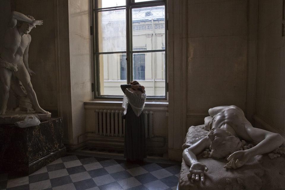 Person steht in einem Raum zwischen zwei Skulpturen an einem Fenster.