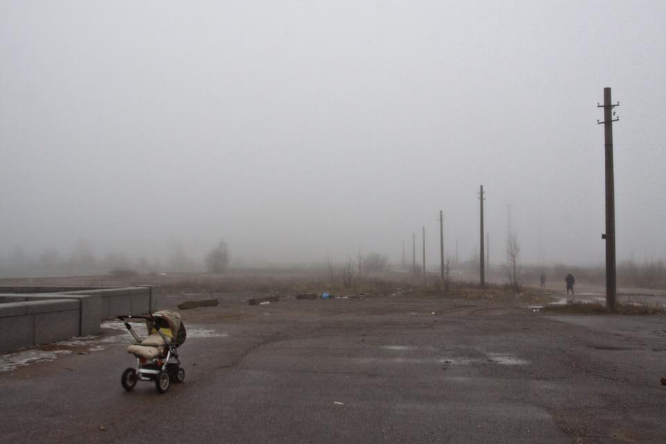 Leerer Kinderwagen vor nebliger, trister Landschaft.