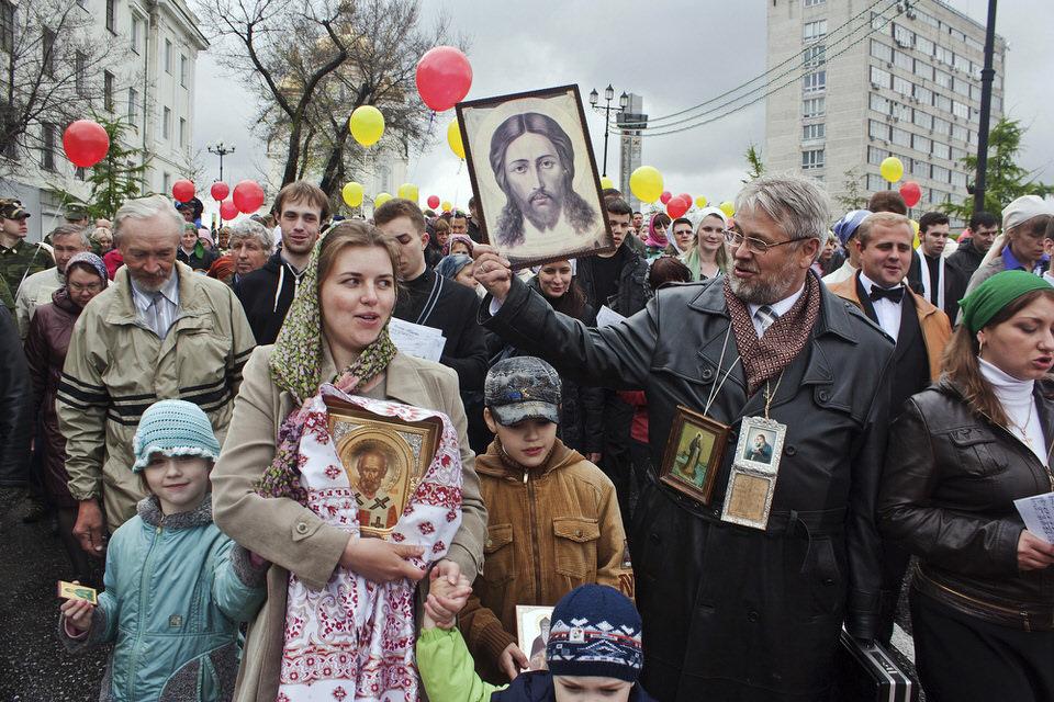 Menschen mit Jesusbildern und bunten Luftballons auf einem Umzug.