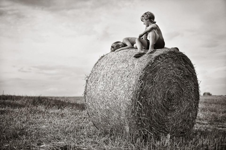 Zwei Kinder auf einem Strohballen.