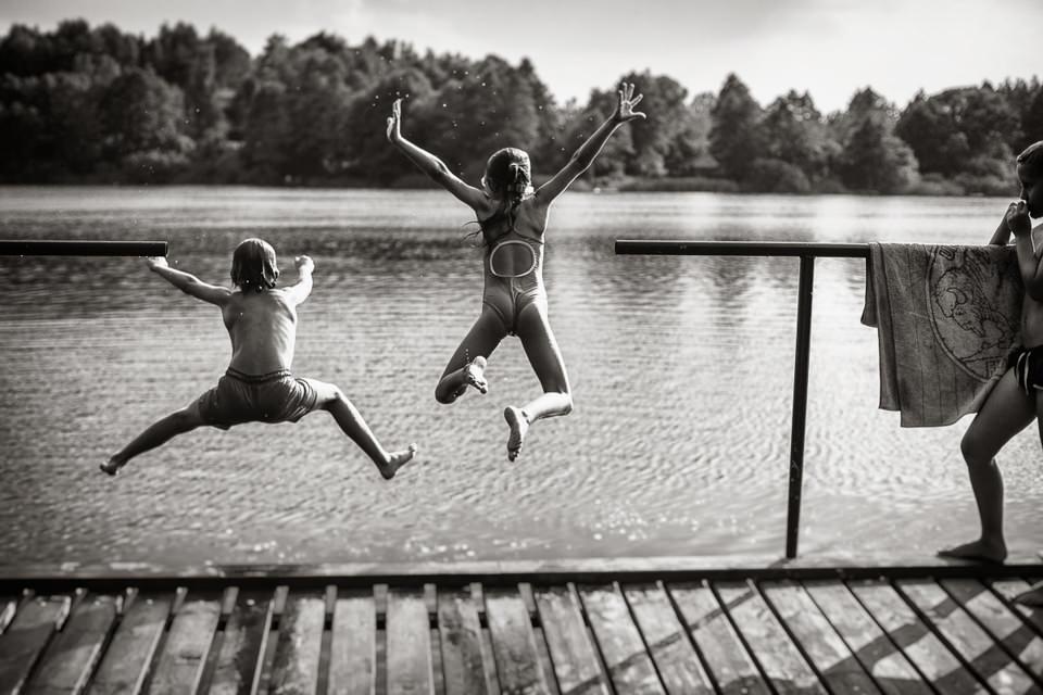 Zwei Kinder springen ins Wasser.