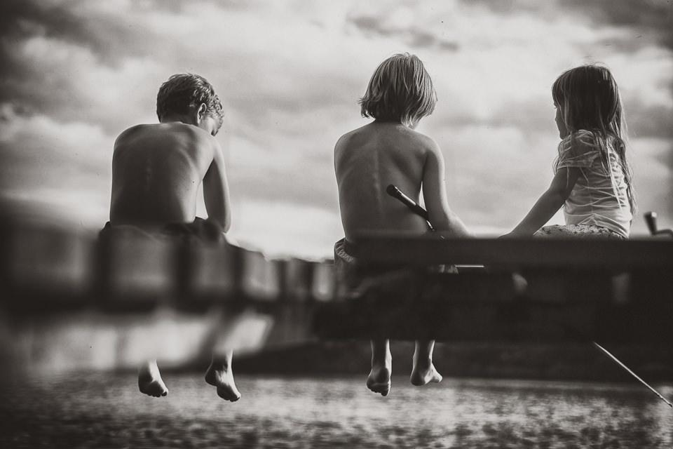 Drei Kinder sitzen auf einem Steg.