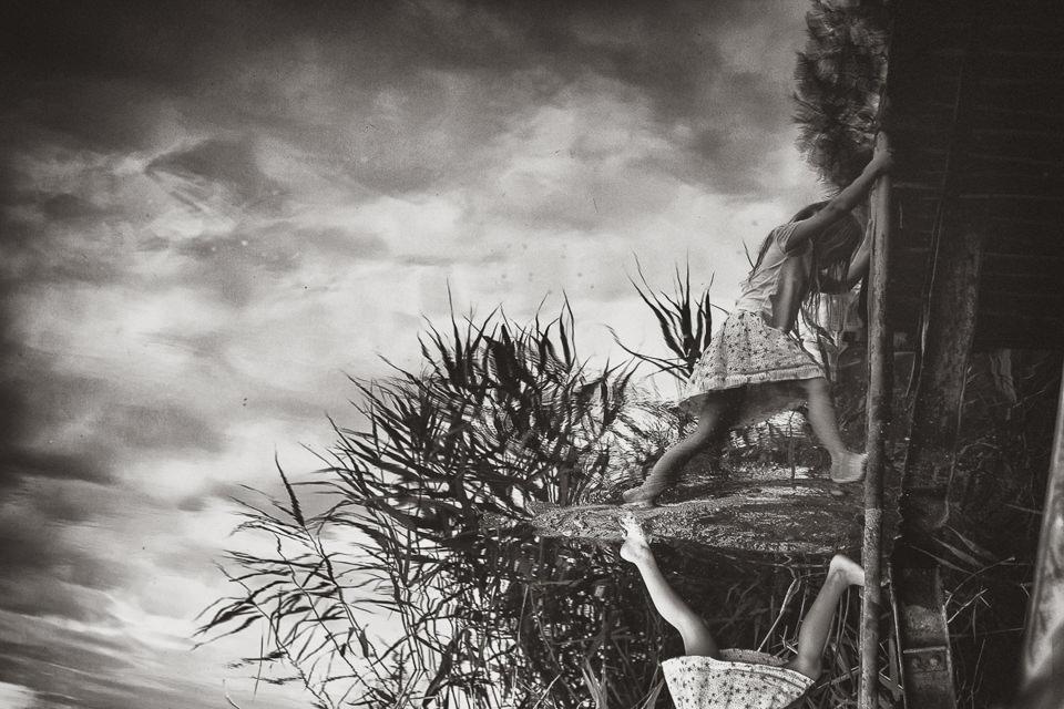 Spiegelbild eines Mädchens an einem Steg.