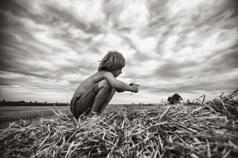 Ein Junge hockt im Stroh.