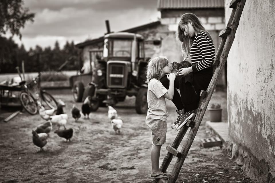 Ein Mädchen sitzt mit einer Katze auf einer Leiter. Ein anderes Kind steht unten und versucht, die Katze zu küssen.