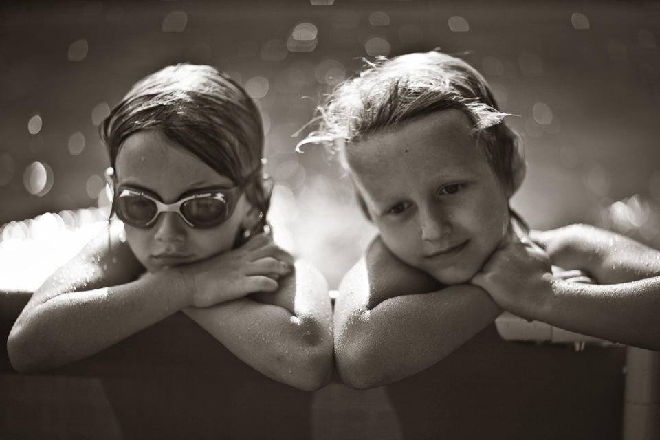 Zwei Kinder am Rande eines Pools.