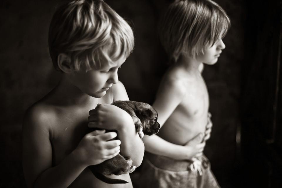Zwei Kinder. Eines hält einen Welpen im Arm.