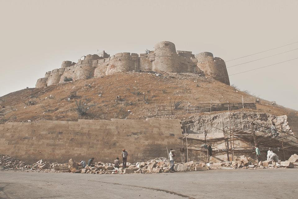Im Vodergrund Bauarbeiter an einer Straße. Dahinter auf einem Berg eine Art Festung.