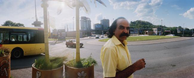 Ein Mann in gelbem Hemd an einer Straßenkreuzung.