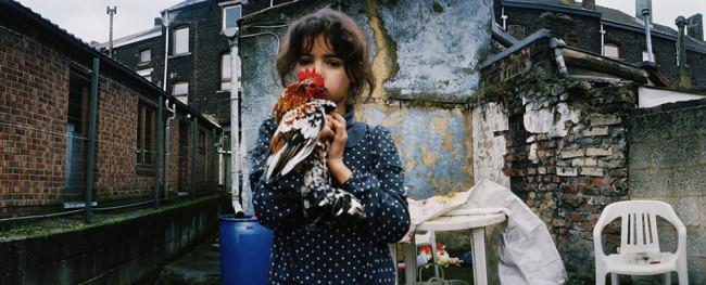 Ein Mädchen mit einem Hahn auf dem Arm, in einem Hinterhof.