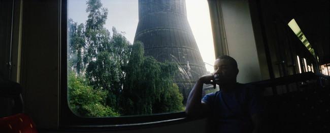 Ein Mann vor einem Zugfenster, durch das man eine Industriegegend sieht.