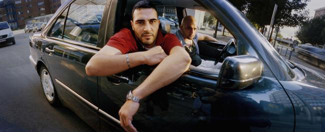Ein Mann hängt lässig aus einem Autofenster.