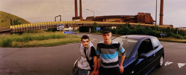 Zwei junge Männer posieren auf einer Motorhaube vor einer Industrielandschaft.