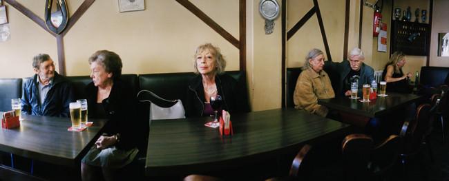 Eine einzelne Frau in einer Kneipe, an den Nebentischen ältere Paare.